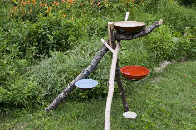 A birdbath structure with three colourful bowls and branches.