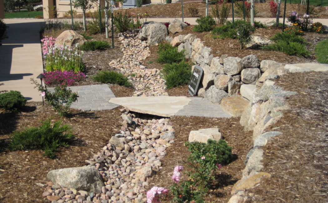 A dry creek bed with a flat stone bridge.