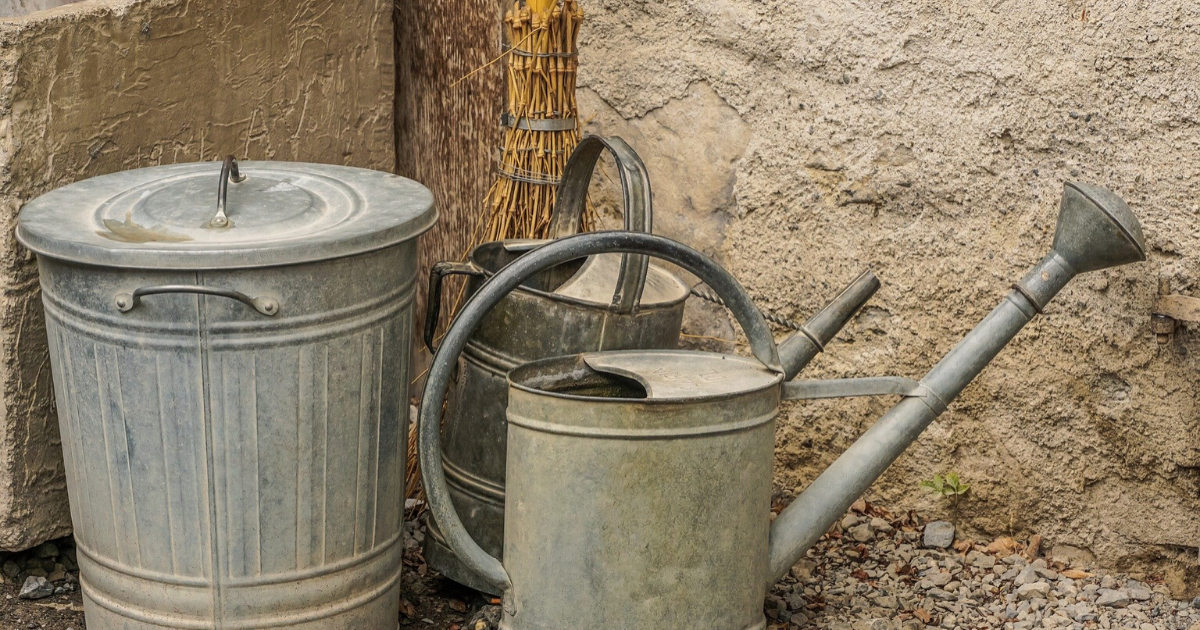 Medium size metal water tank along with two small sizes metal watering cans.
