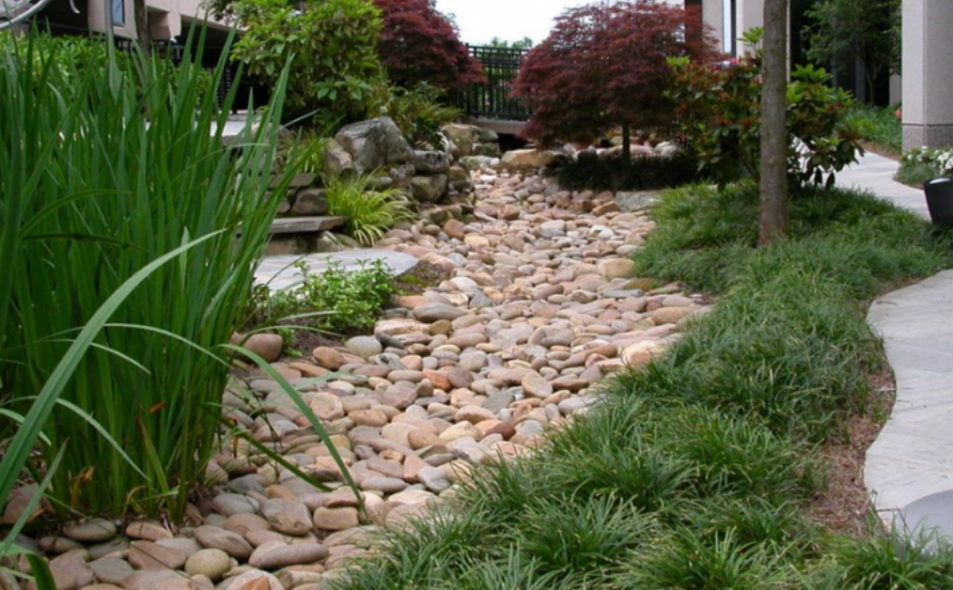 A wide dry creek bed using an earthy shade of rocks.
