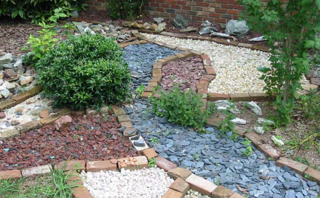 A landscape using blue, red, and white gravels to create a combo of river beds.