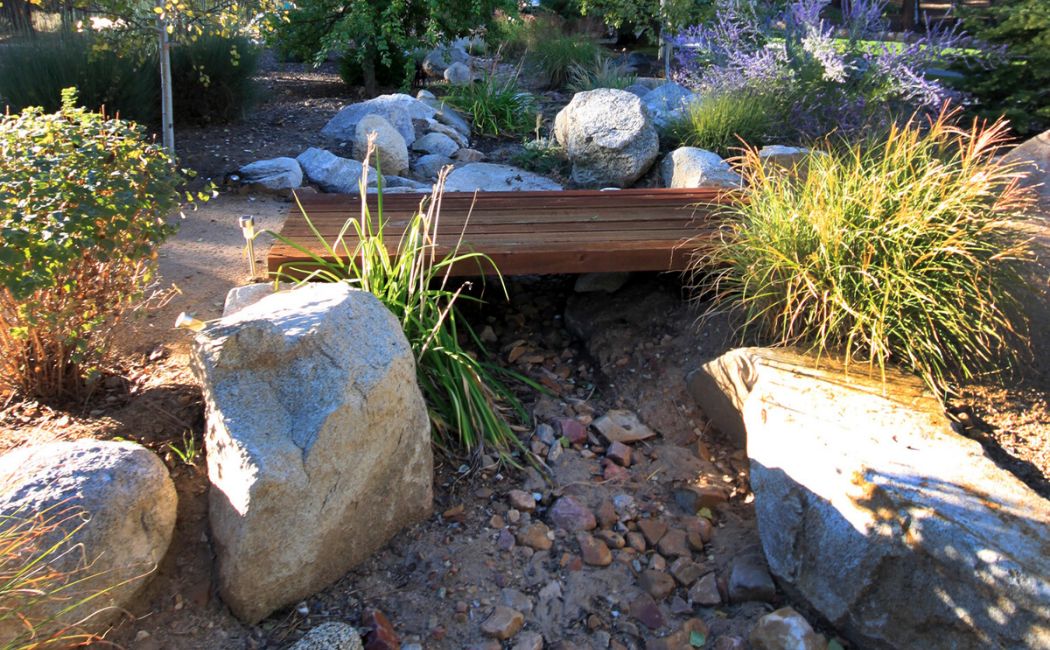 A simple wooden bridge accentuates the simplicity of the dry creek bed.