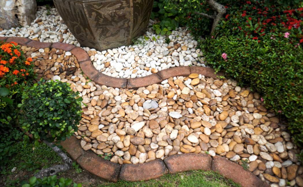 A winding dry river bed separated into a light shade and an earthy shade pebbles.