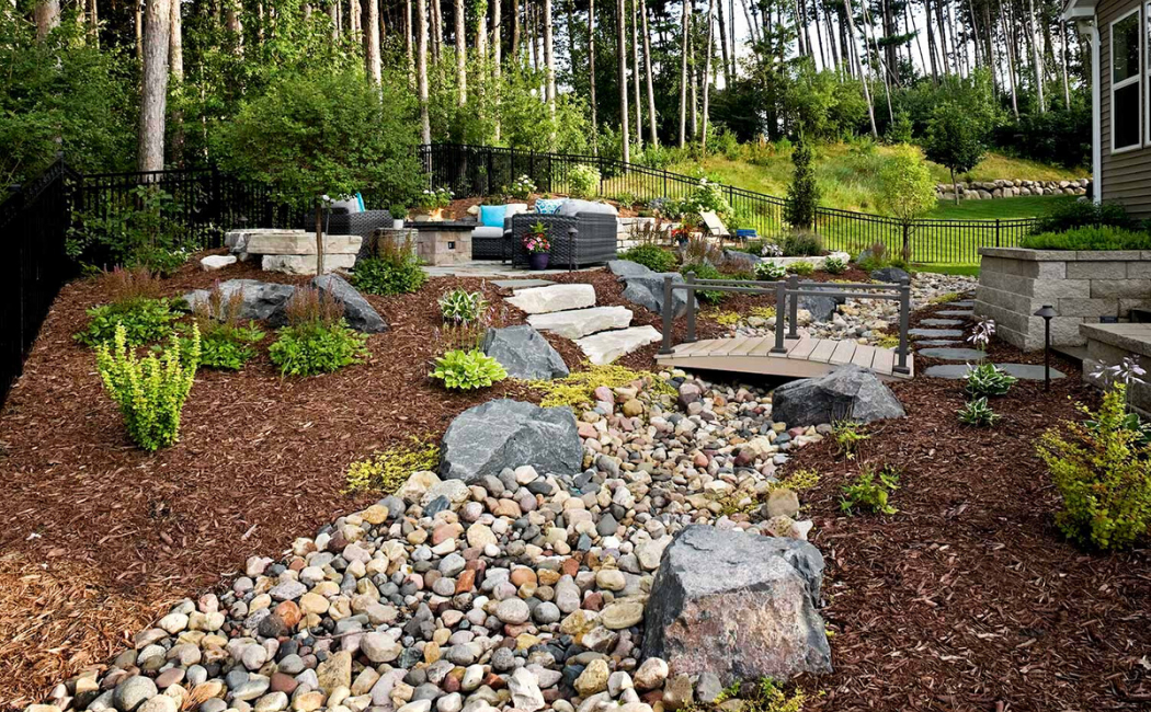A dry creek bed with a wooden bridge in the spacious backyard.