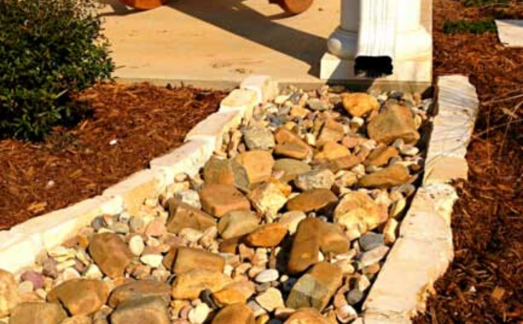 A dry creek with a bed of earthy shade rocks used as water drainage.