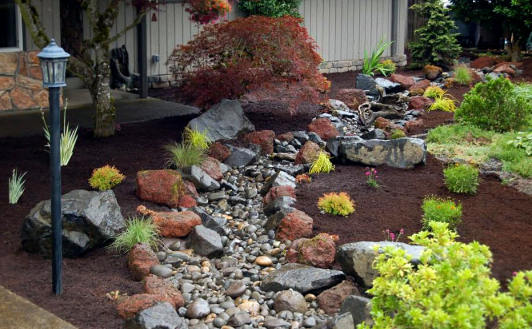 A dry creek bed using red shade border stones.