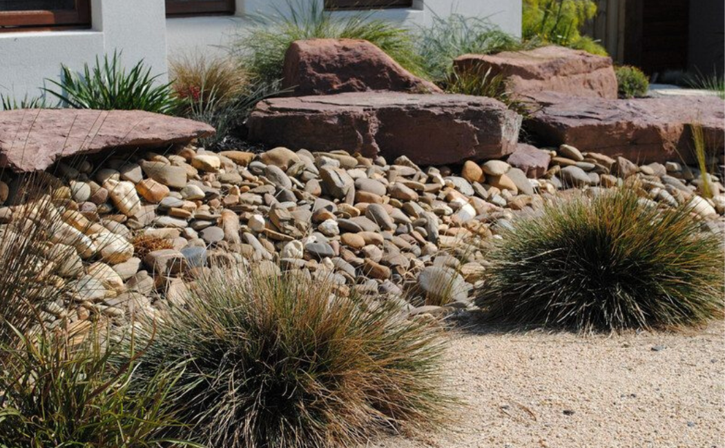 Boulders, rocks, and shrubs making a stunning dry creek landscape.