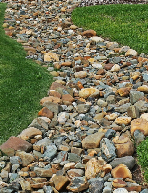 A dry creek with a colourful stone bed.