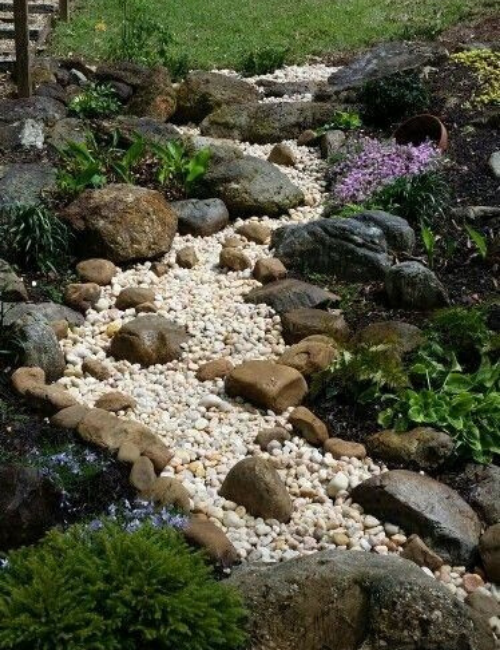 A dry creek with a bed of light-colored stones.