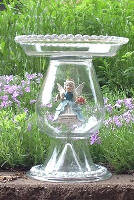An angel inside the glass garden birdbath.