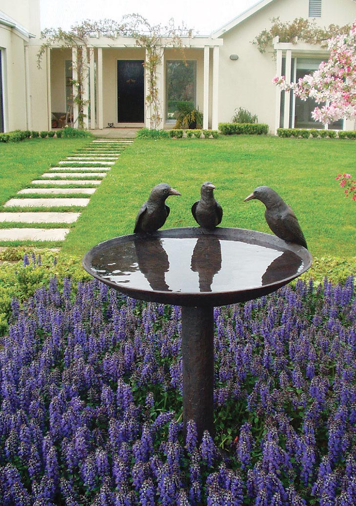 A metal pedestal birdbath with three birds perched on the brim.