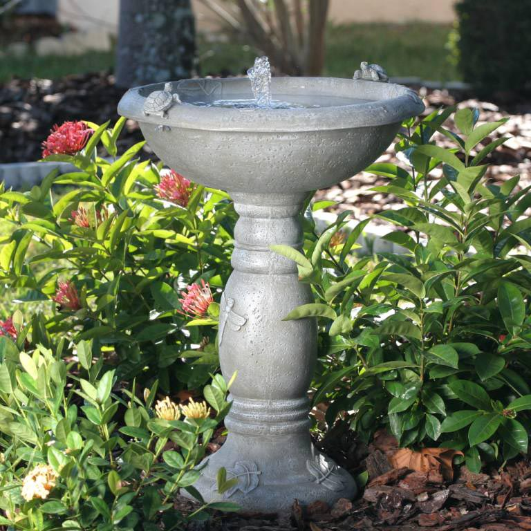 Concrete birdbath with turtles and dragonflies design.