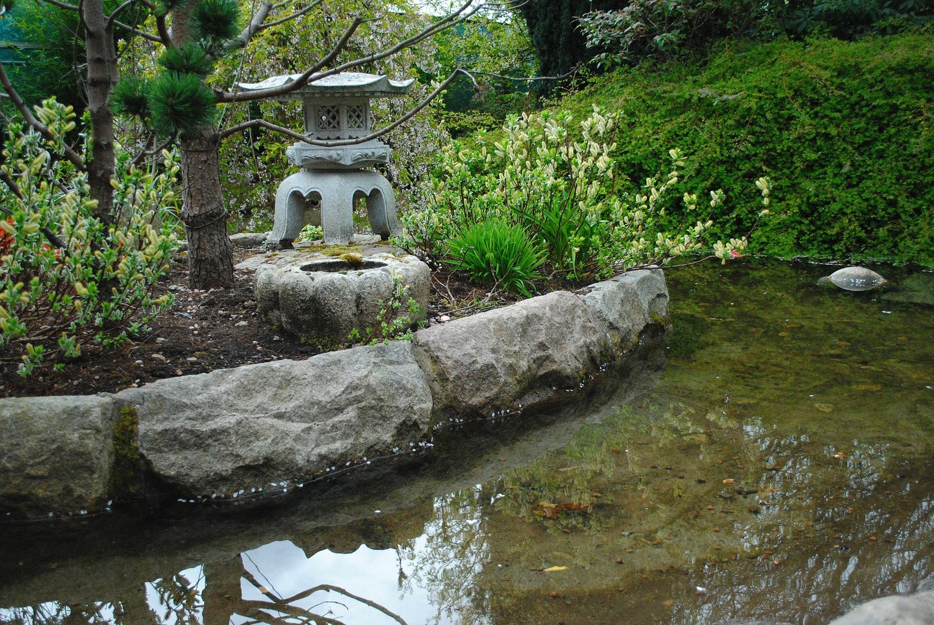 Sculpted stone lantern beside the pond.