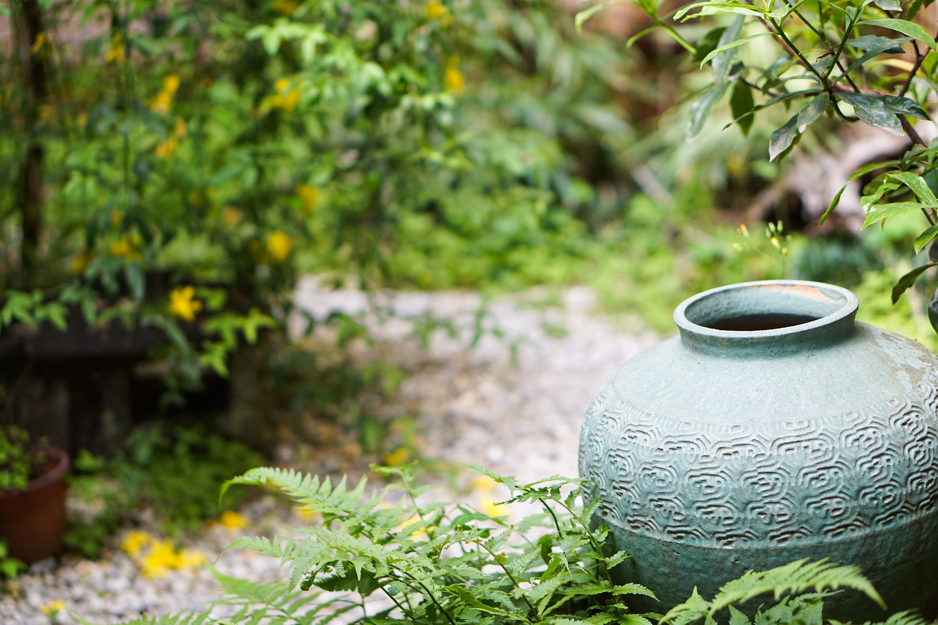 Green big ceramic jar in a garden.