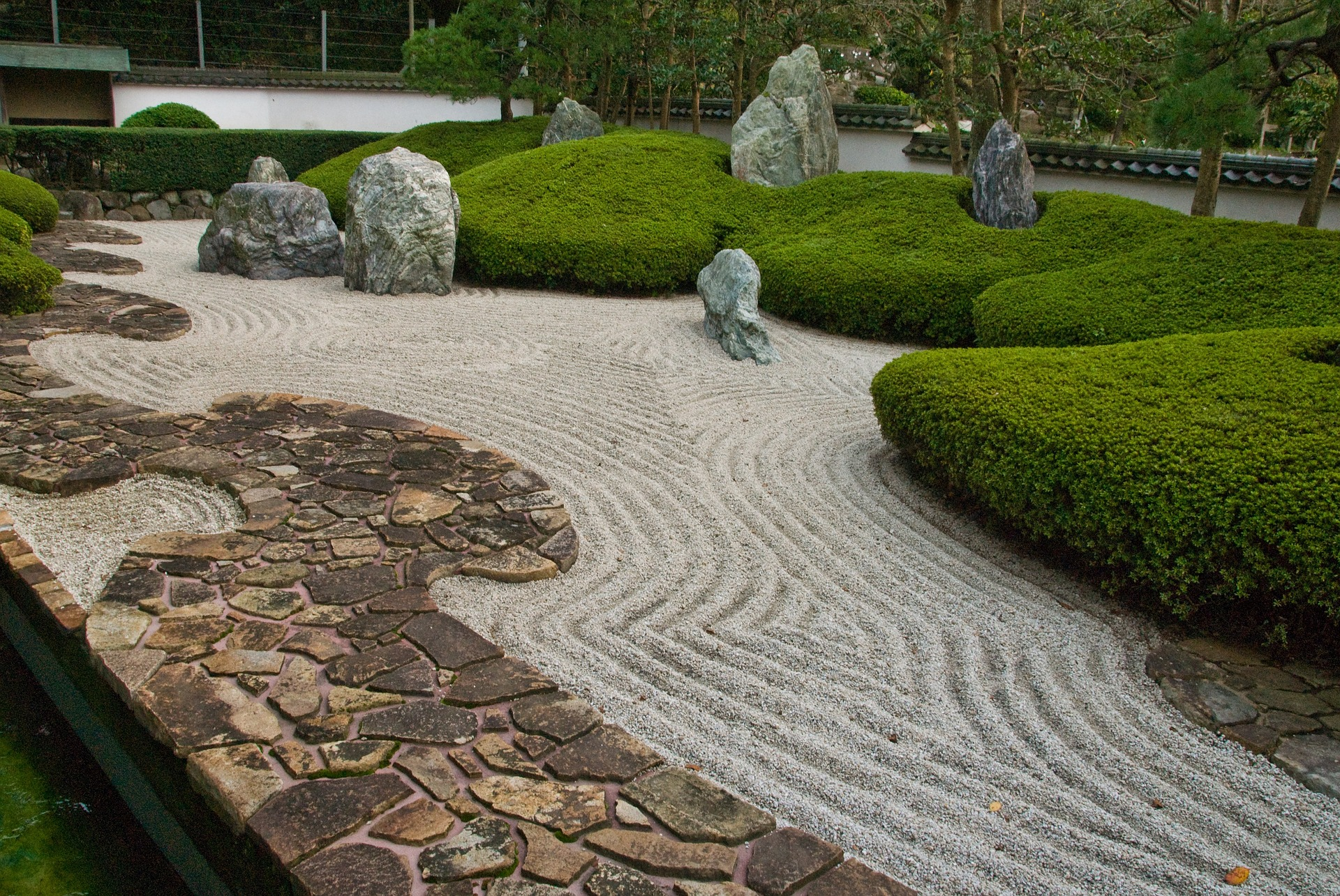 Zen garden with stone path and a pattern of a flowing river.