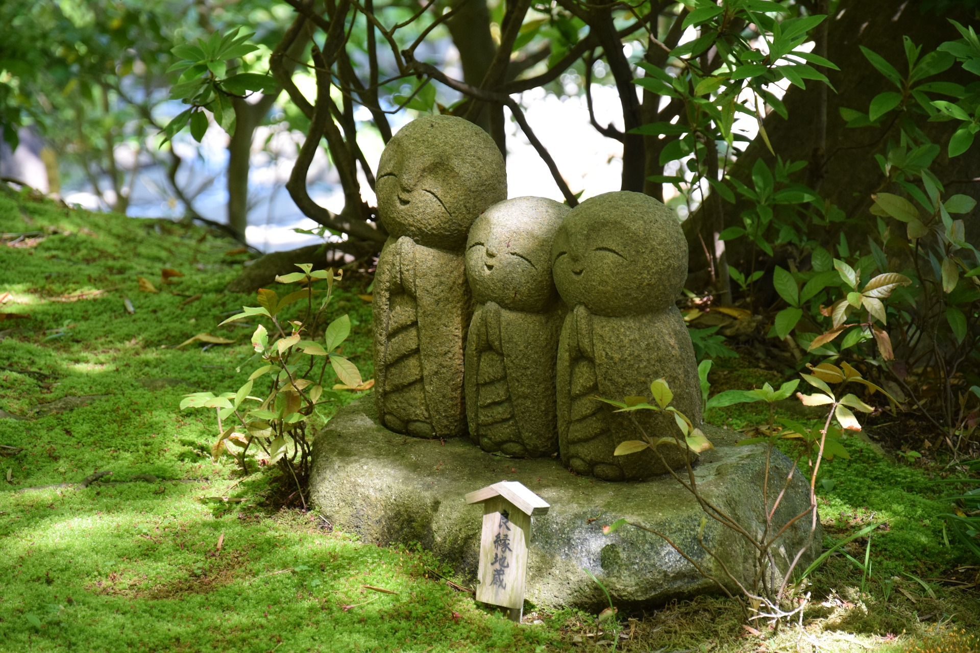Three sculpted figures of fairies in the garden.
