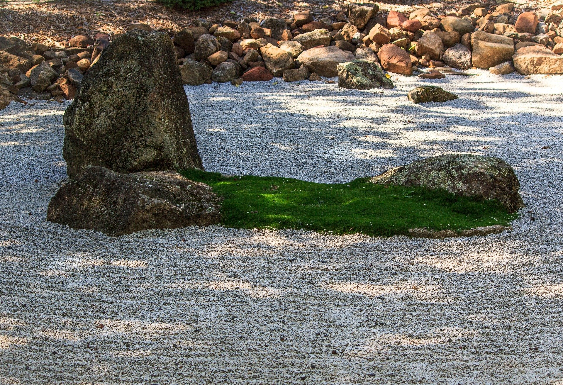 Outdoor zen garden with rocks and moss at the center.