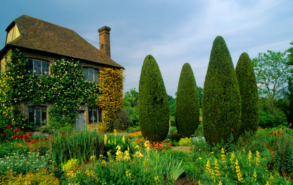 Four pieces of manicured statuary and creeping vines accentuate a spacious garden.