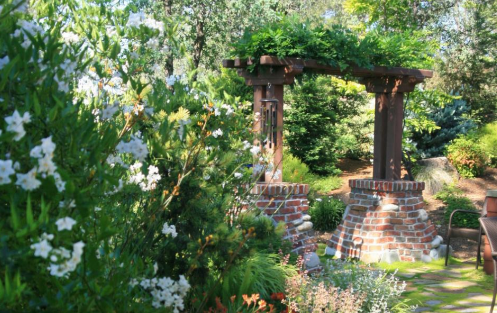 A brick base pergola at the center of a garden.