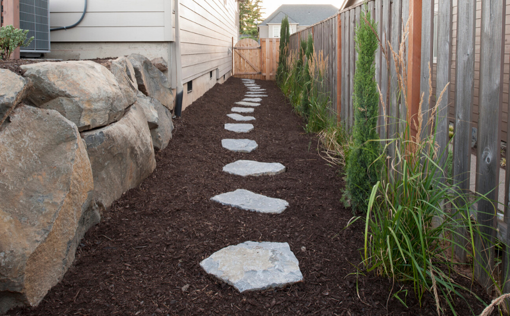 The stone path on dark brown mulch.