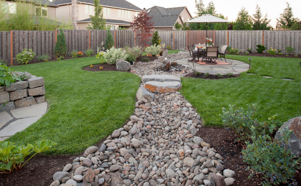 A dry creek bed as the centerpiece of a backyard garden.