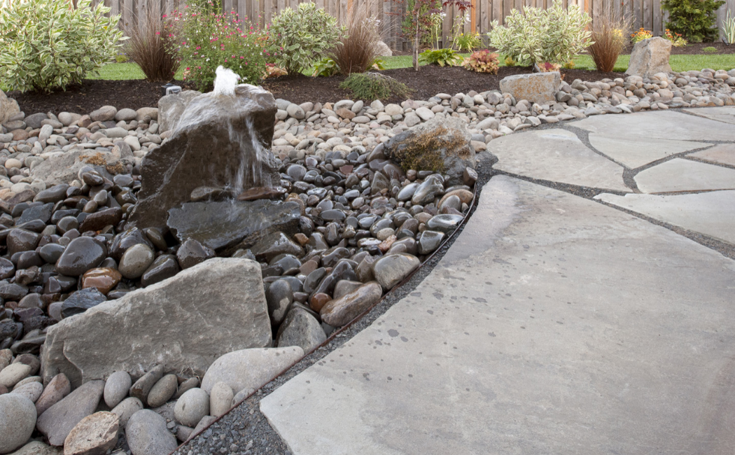 A rock fountain at the center of the yard.