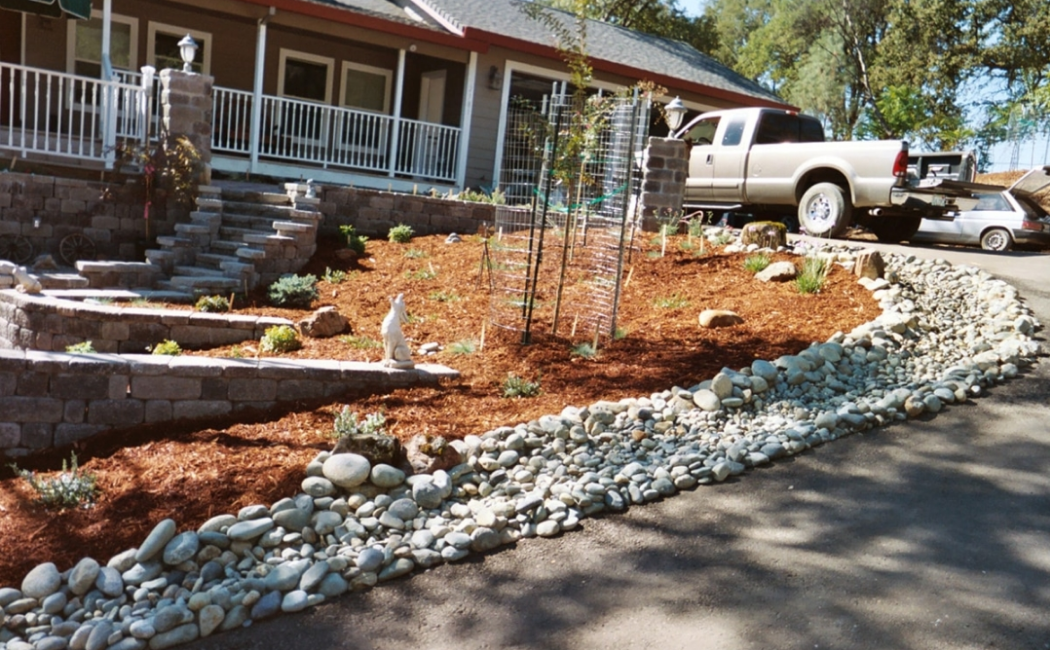 A dry creek bed beside a downward sloped driveway.