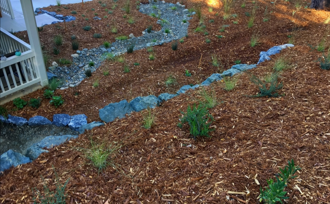 A blue shaded dry creek bed with rocks at the center of the mulch garden.