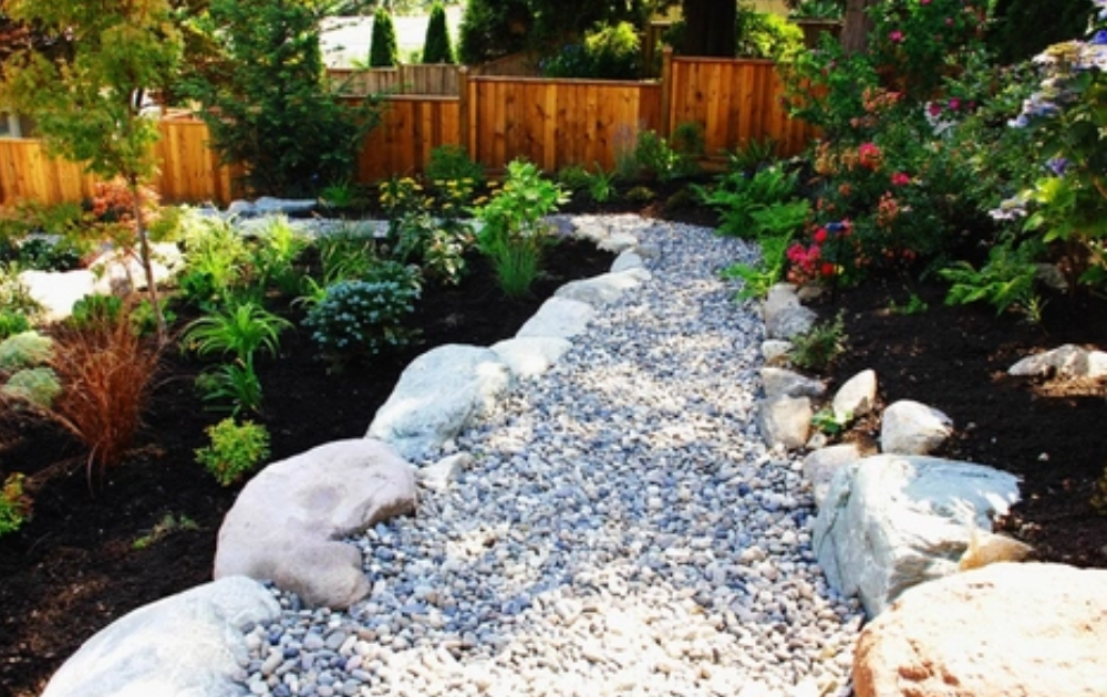 Dry creek bed with white stone border.