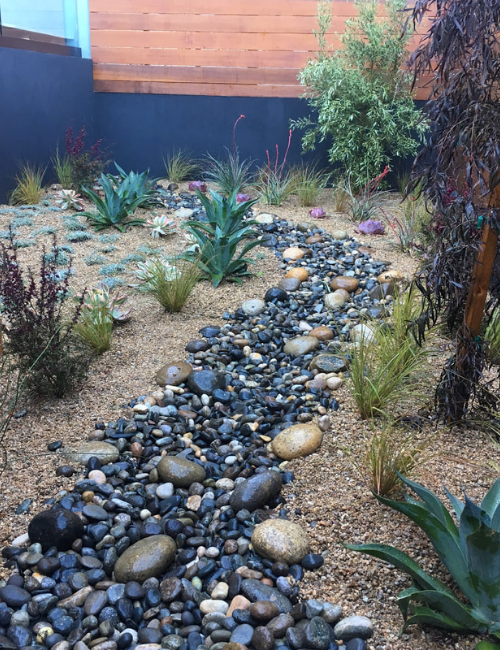 A dry creek with a bed of black shiny stones.