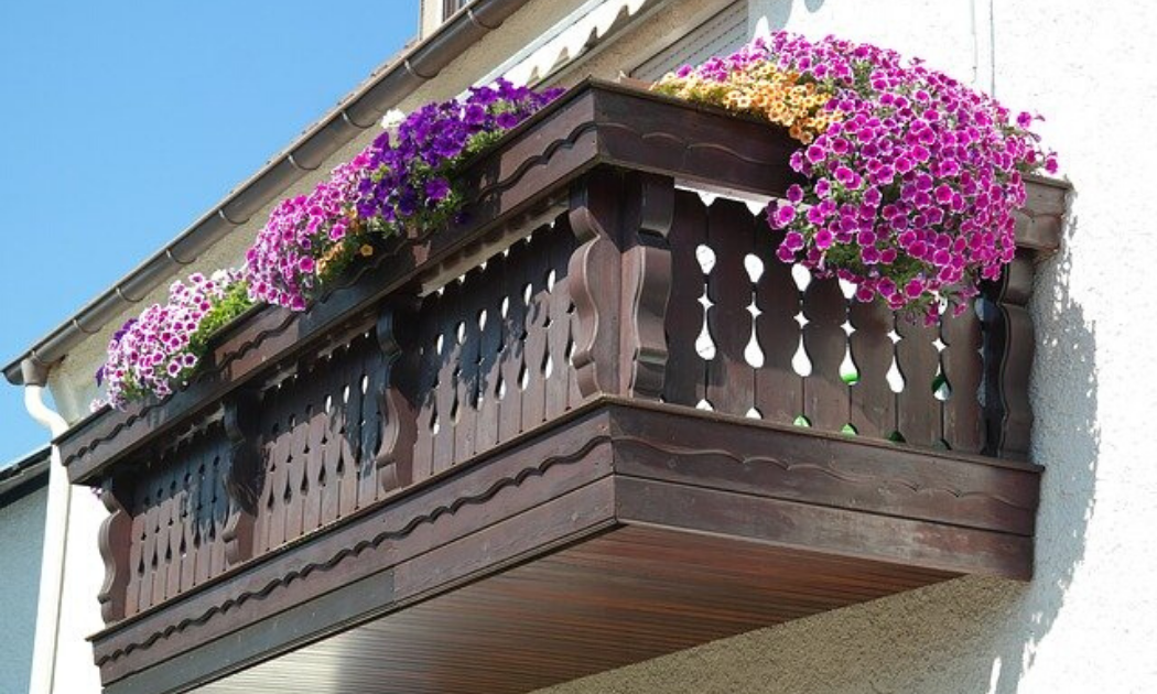 Colorful flowers on a brown wooden balcony.