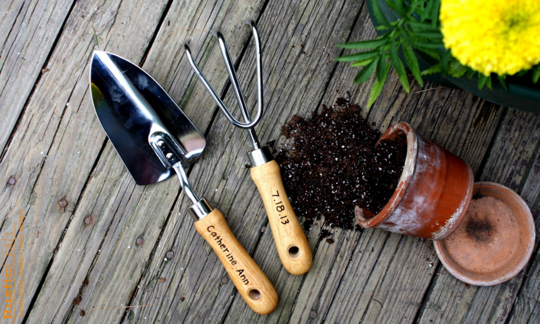 Garden fork and scoop with wooden handle and ceramic pot with potting mix.