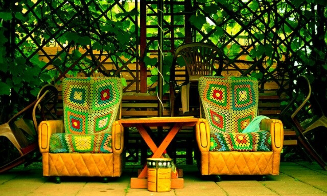 Wooden mini table and two leathered lounge chairs in a terrace garden.