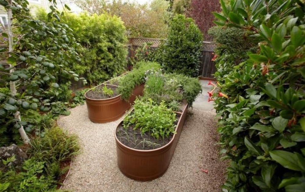 Two galvanized steel raised beds painted brown.