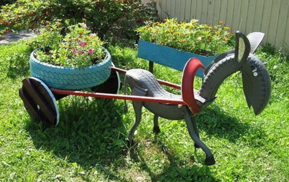 Tire planter with flowering plants carried by horse structure built out of tire.