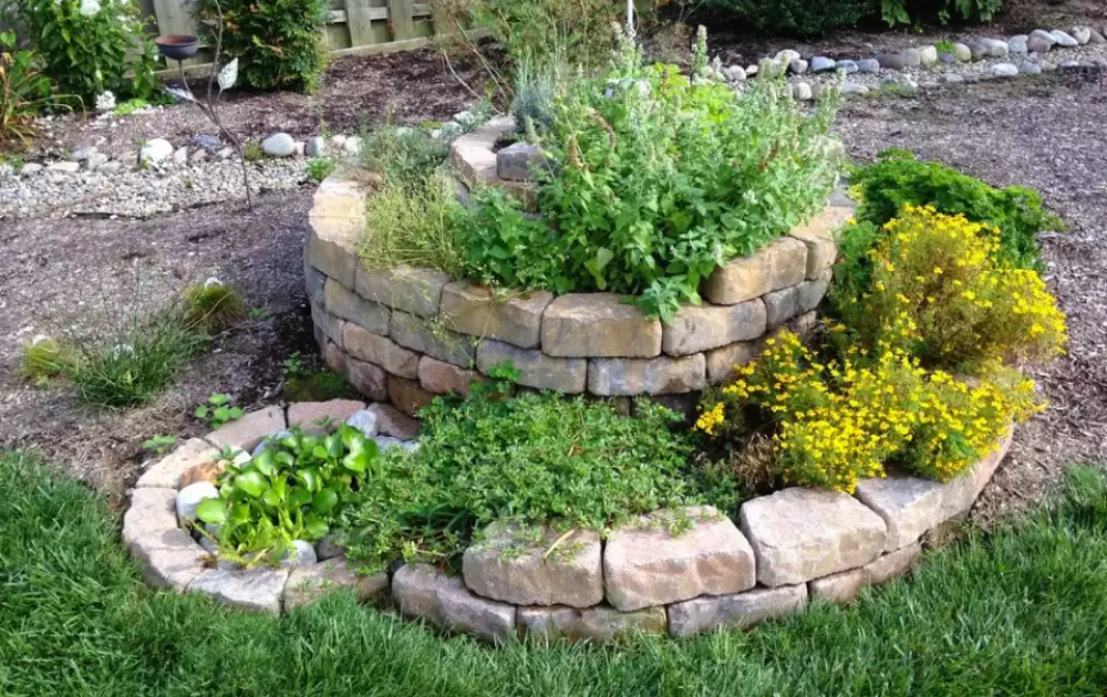 Raised bed built out of boulders and stone with spiral design.