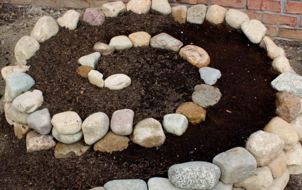 Spiral shape raised bed with fieldstone and mulch.