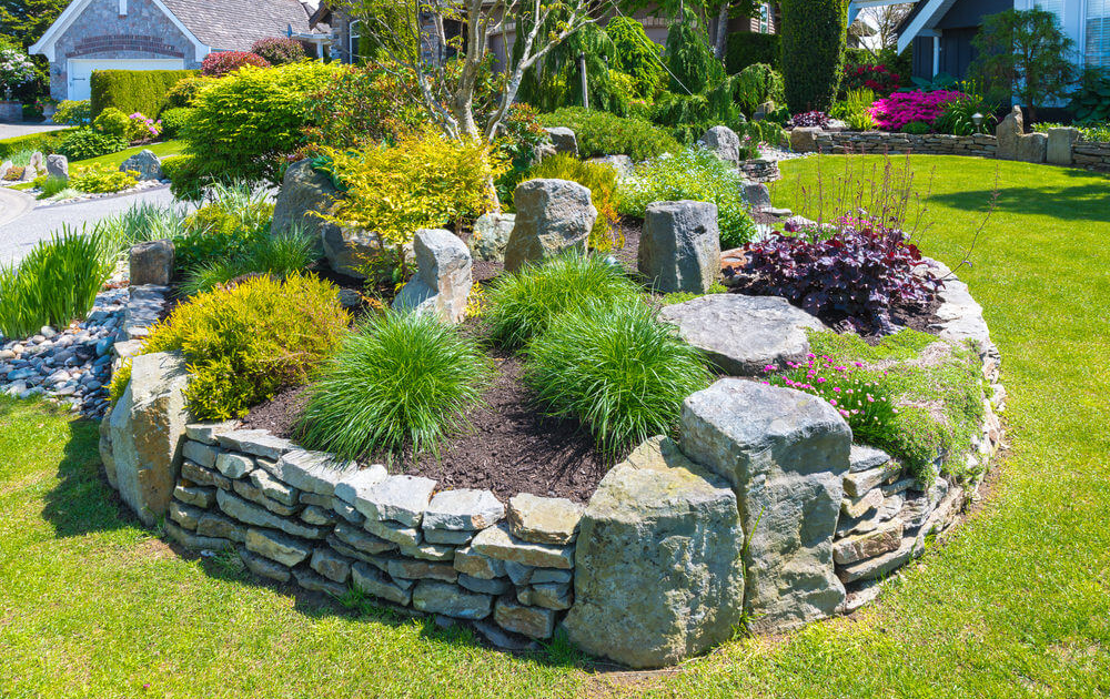 Round raised bed built out of boulders and stones.