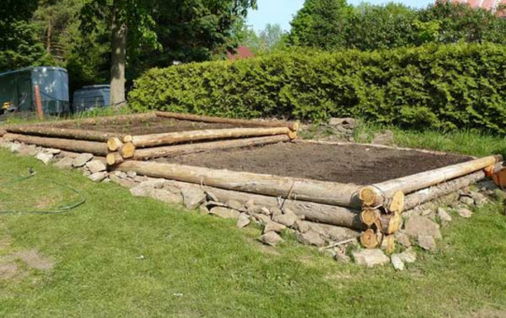 Two-tiered square raised beds built out of logs.