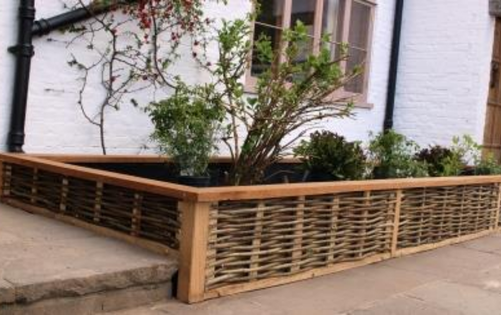 Sideyard wattle raised bed with the wooden frame structure.