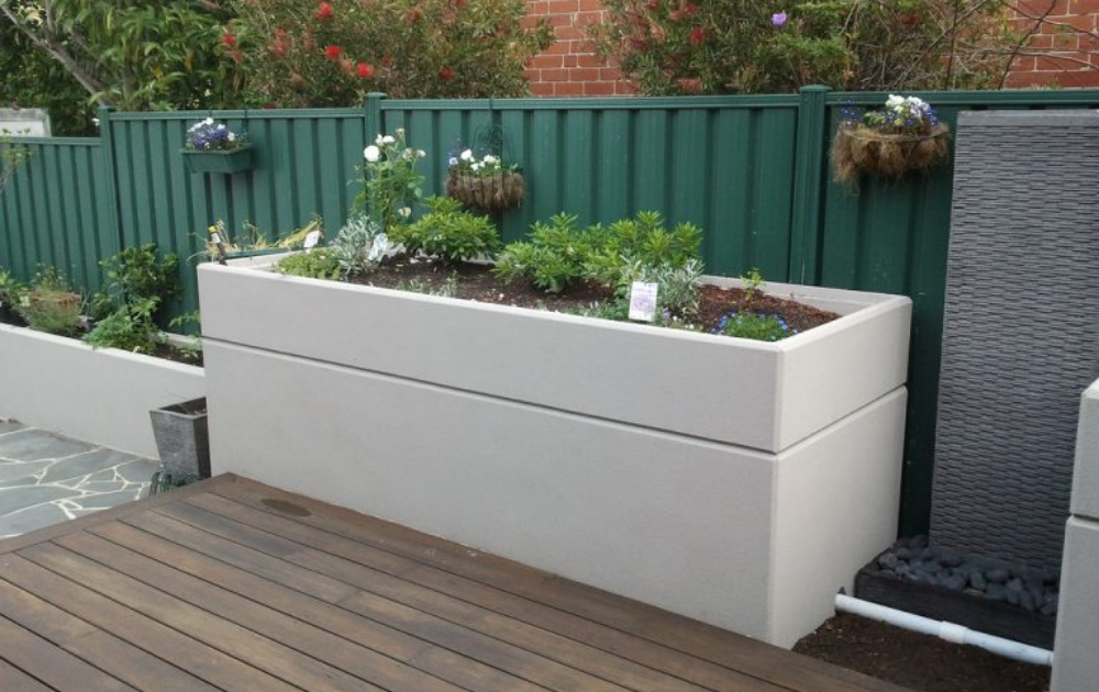 Box shape raised bed built out of concrete in white finish with growing rosemary.