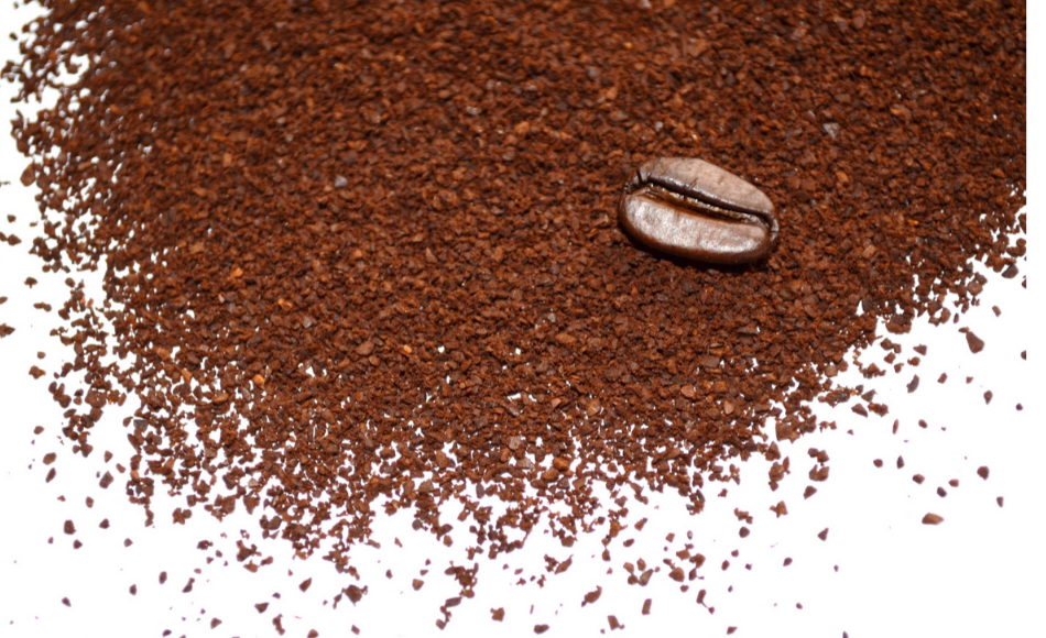 Ground coffee and a bean on a table.