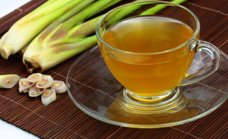 A cup of lemongrass tea in a saucer along with a few slices and two whole lemongrass stalks.