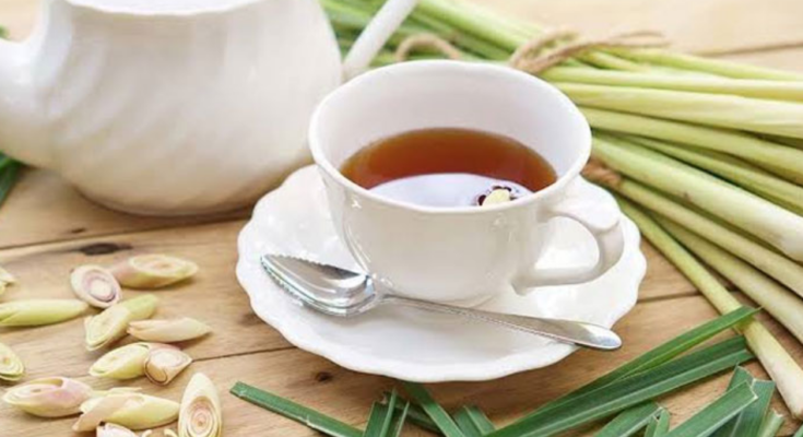 A pair of white ceramic cup and saucer filled with lemongrass tea on the table.