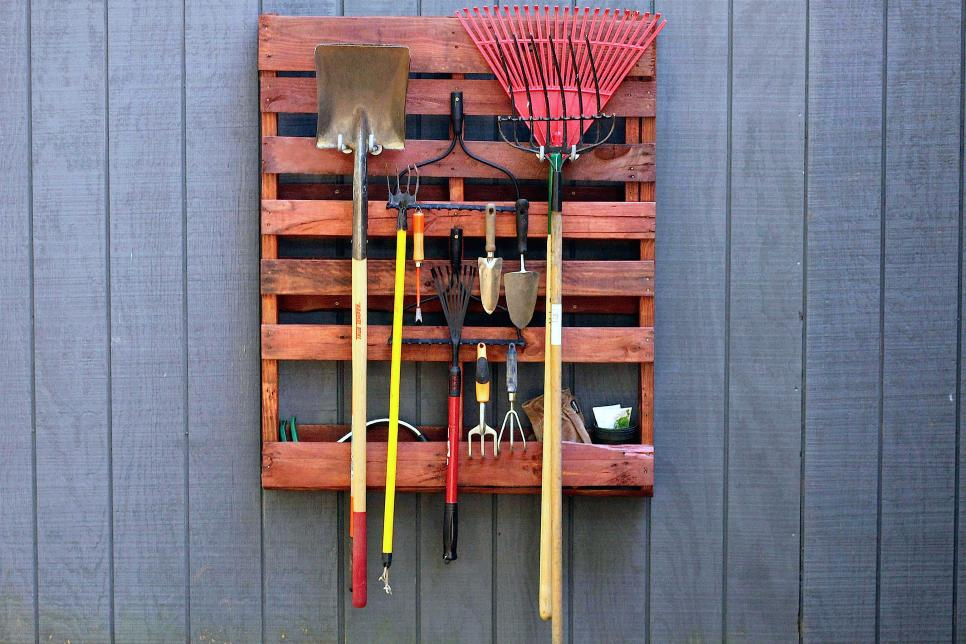 Stained pallet hung on the wall as garden tool storage.