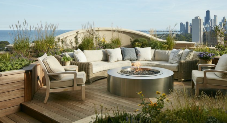 This rooftop garden features comfortable seating with cushions and throw pillows. It has a circular fireplace at the centre and flowering plants just below the safety barrier.