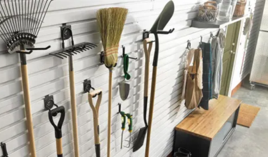 Hanging garden tools on the heavy-duty hardware black hooks attached to the garage side wall.
