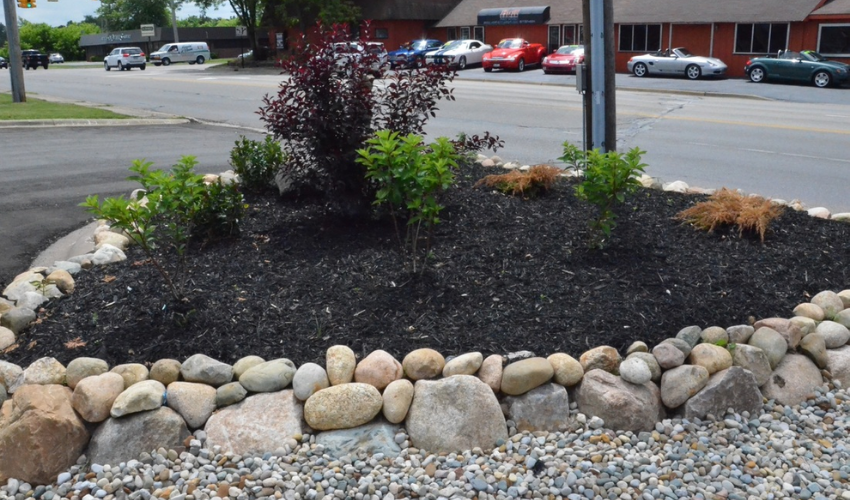 Ornamental garden bed with black mulch and stone border beside the street.