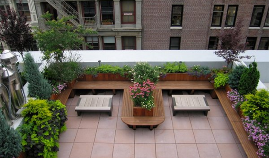 The rooftop garden displays a U-shaped wooden seating that also serves as built-in planters with flowering plants. It has a center table with two small chairs on both sides.