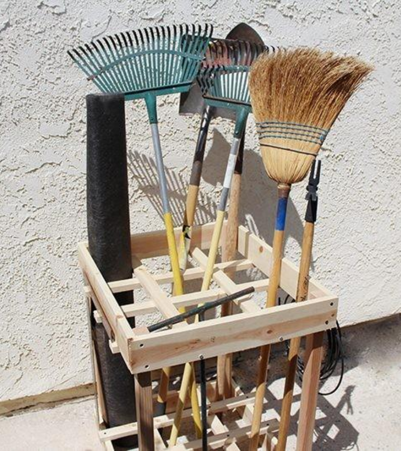 Wooden crisscrossed box garden tool storage with long-handled shovels, rakes and broom.